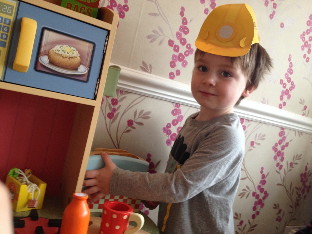 The birthday boy, playing with his new kitchen whilst wearing a very cool construction party hat from Little Lulubel!