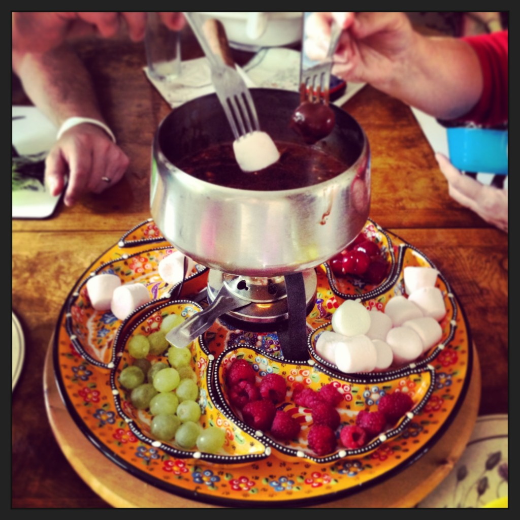 Everybody dipping fingers into a fondue pudding at our dinner table.